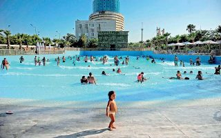 A child walks past as visitors swim in an artificial wave pool at the Isla Magica theme park in Andalusia, in Sevilla on July 21, 2015. Spaniards braved the second day of the country's third heatwave this summer as 18 provinces were placed on alert for high temperatures by the Spanish meteorological agency. AFP PHOTO/ CRISTINA QUICLER