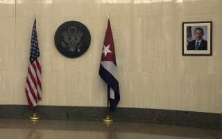 The flags of the United States (L) and Cuba are placed beside the seal of the United States and near a photograph of U.S. President Barack Obama in the entrance hall of the U.S. embassy in Havana, Cuba, August 14, 2015. U.S. Secretary of State John Kerry travels to Cuba on Friday to raise the U.S. flag at the recently restored American embassy in Havana, another symbolic step in the thawing of relations between the two Cold War-era foes. REUTERS/Enrique De La Osa