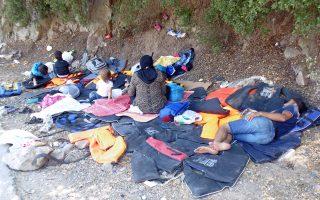 Πρόσφυγες ξεκουράζονται πάνω σε σωσίβια στη Μυτιλήνη, μετά την άφιξή τους στο νησί.