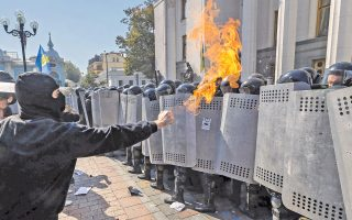 Διαδηλωτές που αντιδρούν στο επίμαχο ν/σ που παρέχει αυτονομία στους ρωσόφωνους της ανατολικής Ουκρανίας συγκρούονται με δυνάμεις ασφαλείας έξω από το Κοινοβούλιο, στο Κίεβο.