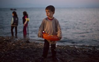 Το αγοράκι από τη Συρία έχει μόλις κατέβει από το πλωτό βαρκάκι στην Κω και δεν θέλει να βγάλει το σωσίβιό του... (A.P. Photo/Alexander Zemlianichenko).