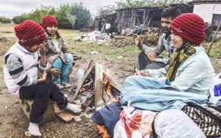 Μια οικογένεια Αφγανών κάθεται γύρω από μια φωτιά στη σερβική πόλη Πρέσεβο.