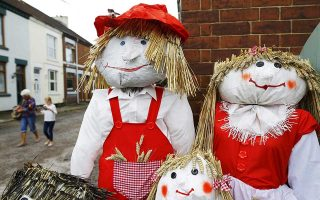 Visitors walk past a family of scarecrows during the Scarecrow Festival in Heather, Britain July 29, 2015. The annual event asks residents of Heather to make scarecrows to raise thousands of pounds for local groups and charities.   REUTERS/Darren Staples