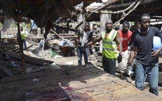 Rescue workers at the site of  a suicide bomb attack at a market in Maiduguri , Nigeria, Tuesday, June 2, 2015.  Boko Haram attacked the northeastern Nigerian city of Maiduguri on Tuesday with deafening explosions from the west and a suicide bombing near the center that witnesses said killed as many as 20 people.  (AP Photo/Jossy Ola)