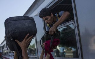 Refugees transport their luggage onto a train, in  Beli Manastir, near the border between Croatia and Hungary, Friday, Sept. 18, 2015. Croatia is trying to move along the thousands of people who have arrived in the country over the past few days, but Slovenia does not want to let them in. Most want to move on to countries like Germany and Sweden. (AP Photo/Manu Brabo)