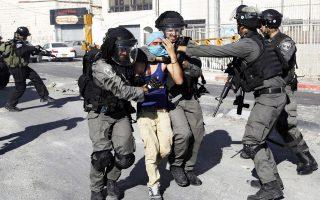 Ισραηλινός αστυνομικός συλλαμβάνει νεαρό Παλαιστίνιο στην Ιερουσαλήμ.