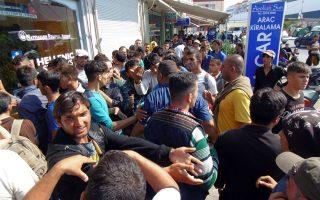 Πλήθος μεταναστών και προσφύγων έξω από εκδοτήρια εισιτηρίων στο λιμάνι της Μυτιλήνης.