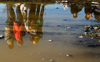 epa04942188 ROTATED REPEAT of epa04942167 =  Migrants are reflected in a puddle as they are waiting for a permission to move towards the train station at a refugee camp near Gevgelija, The Former Yugoslav Republic of Macedonia, 21 September 2015. The main migration route across the Balkans - from Turkey, across Greece, Macedonia and Serbia - previously led to Hungary. But after Hungary sealed its borders, migrants began taking an alternative route to Western Europe via Croatia, the EU's newest member.  EPA/NAKE BATEV  EPA/NAKE BATEV ROTATED REPEAT