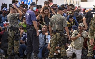 epa04930179 Migrants and refugees wait for permission to board a train heading to the border with Serbia, near the town of Gevgelija, The Former Yugoslav Republic of Macedonia, 14 September 2015. The Gevgelija-Presevo journey is just a part of the journey that the refugees, the vast majority of them from Syria, are forced to make along the so-called Balkan corridor, which takes them from Turkey, across Greece, Macedonia and Serbia.  EPA/GEORGI LICOVSKI