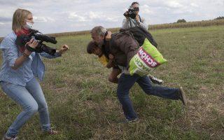 Η Πέτρα Λάζλο λίγο πριν «καλωσορίσει»με τρικλοποδιά τον πρόσφυγα με το παιδί στην αγκαλιά.