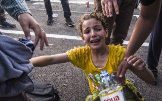 Ενα κοριτσάκι κλαίει αφού δέχθηκε δακρυγόνα που έριξε η ουγγρική αστυνομία εναντίον μεταναστών και προσφύγων στο σερβικό έδαφος.