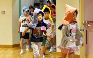 Elementary school children wear fireproof hoods as they take part in an earthquake drill at a school in Tokyo on September 1, 2015. Nationwide anti-disaster drills were held on September 1 on the anniversary of the massive 1923 earthquake which killed more than 100,000 people in the Tokyo metropolitan area.   AFP PHOTO/Yoshikazu TSUNO