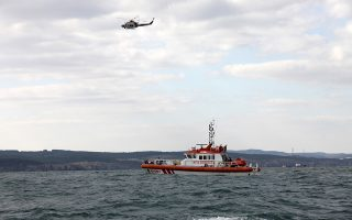 A Turkish coastguard boat and helicopter search for possible survivors near the remains of a boat carrying suspected migrants from Afghanistan and Syria that sank just north of the Bosphorus Strait off the coast of Istanbul, Turkey, Monday, Nov. 3, 2014, leaving at least 24 people dead and several people missing. Seven people were rescued, Turkish authorities said.(AP Photo)