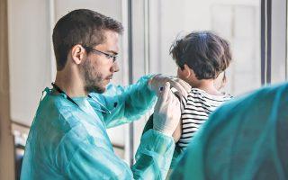 O εθελοντής γιατρός του Nοσοκομείου «H Aγία Σοφία» εμβολιάζει το προσφυγόπουλο...