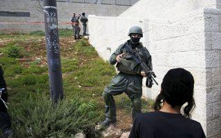 Νεαρός ορθόδοξος Εβραίος παρατηρεί Ισραηλινό στρατιώτη κατά τη διάρκεια επιχείρησης των δυνάμεων ασφαλείας χθες στην Ιερουσαλήμ.