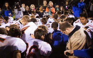 Διαχωρισμός θρησκειών. Με αναγκαστική άδεια τιμωρήθηκε ο βοηθός προπονητή του σχολείου  Bremerton του Σιάτλ για την ανυπακοή του στις υποδείξεις του σχολείου. Και ποιες ήταν αυτές; Να μην προσεύχεται στους αγώνες ποδοσφαίρου. Στην φωτογραφία ο Joe Kennedy (με την μπλε φόρμα) και τους αθλητές του σε μια ομαδική προσευχή στο τέλος ενός αγώνα. Σύμφωνα με το σχολείο πρέπει να αποφεύγονται οι δημόσιες εκδηλώσεις θρησκευτικής λατρείας, σύμφωνα με τους φανατικούς της μπάλας, υποταγή δηλώνουμε μόνο στην στρογγυλή θεά.  Lindsey Wasson/The Seattle Times via AP