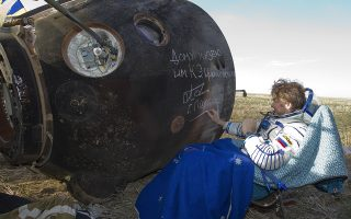 TOPSHOTSInternational Space Station (ISS) crew member Russian cosmonaut Gennady Padalka signs an autograph on the Soyuz capsule after the landing near the town of Arkalyk in northern Kazakhstan, on September 17, 2012. A woman took today command of the ISS for only the second time as three US and Russian colleagues made a safe return from the orbiting space lab to the Kazakh steppe. AFP PHOTO / POOL/ SHAMIL ZHUMATOV
