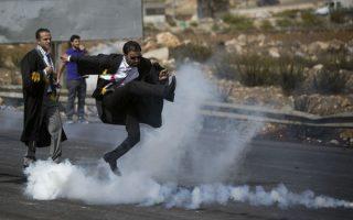 Ο μπαλαδόρος δικηγόρος. Φορώντας τα επίσημα ρούχα τους με τα οποία παραβρίσκονται στο δικαστήριο, το σωματείο των δικηγόρων της Παλαιστίνης συμμετείχε σε διαδήλωση με αφορμή τα πρόσφατα επεισόδια στα οποία 25 Παλαιστίνιοι έχουν βρει το θάνατο από δυνάμεις ασφαλείας του Ισραήλ (και πέντε Ισραηλίτες από Παλαιστίνιους). Ο δικηγόρος της φωτογραφίας δεν περιορίστηκε από το κοστούμι και το δετό παπούτσι και δεν δίστασε με άψογο στιλ και δυνατό σουτ να επιστρέψει το δακρυγόνο από εκεί που ήρθε. (AP Photo/Majdi Mohammed)