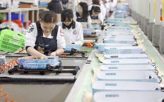 Εργαζόμενοι σε σειρά παραγωγής σε εργοστάσιο στην Τέναν, βόρεια της Ταϊβάν. Η επιβράδυνση της Κίνας, δεύτερης μεγαλύτερης οικονομίας στον κόσμο ενδέχεται να οδηγήσει σε ύφεση πολλές χώρες της Ασίας. Το ΔΝΤ εκτιμά ότι η πτώση του ΑΕΠ της Κίνας κατά 1% αφαιρεί 0,3% από τη γενικότερη ανάπτυξη της Ασίας.