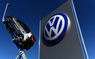 A model and logo of German car maker Volkswagen (VW) are seen at the entrance to a VW branch in Duesseldorf, western Germany, on September 28, 2015.  Volkswagen came under pressure after reports surfaced concerning the manipulation of values of emission in VW vehicles equipped with diesel engines. AFP PHOTO / PATRIK STOLLARZ.