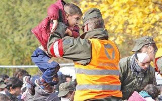 Αυστριακός στρατιώτης περνάει ένα παιδί πάνω από τον φράχτη, καθώς οι πρόσφυγες περιμένουν στο πέρασμα Σπίλεφελντ με τη Σλοβενία.