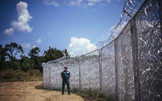 A border policeman stands next to a barbed wire wall on the Bulgarian border with Turkey, near the village of Golyam Dervent on July 17, 2014. Overwhelmed by an influx of mostly Syrian immigrants, Bulgaria has taken steps to secure its EU border -- including building a barbed-wire fence -- but now faces criticism from rights groups. The 30-kilometre (19-mile) fence, standing three metres (10 feet) high and fortified with razor wire coils, was completed this week. Covering the least visible section of Bulgaria's 275-kilometre (170-mile) border with Turkey, it aims to stem a flow of refugees that saw more than 11,000 people enter the country illegally last year -- 10 times the annual figure before the Syrian conflict.   AFP PHOTO / DIMITAR DILKOFF
