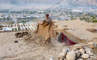Ανδρας καθαρίζει τη σκεπή του σπιτιού του από τα μπάζα ύστερα από τον χθεσινό σεισμό.