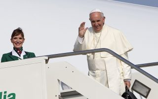 Pope Francis waves to reporters at Rome's Fiumicino International airport, Sunday, July 5, 2015, as he boards his flight to Quito, Ecuador, where he will start a week-long trip to South America, including Bolivia and Paraguay. Francis is taking his