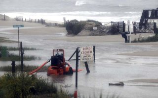 A pump sits in the middle of a flooded street in Ocean Isle Beach, N.C., Sunday, Oct. 4, 2015. Numerous roads in Brunswick and New Hanover counties in southeastern North Carolina are impassable as a storm system that inundated South Carolina moves north. (Mike Spencer/The Star-News via AP)  LOCAL TELEVISION OUT; LOCAL INTERNET OUT; MANDATORY CREDIT