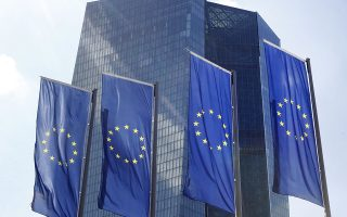FILE - In this July 6, 2015 file photo, European Union flags wave in front of the headquarters of the European Central Bank in Frankfurt, Germany, the day after Greece voted