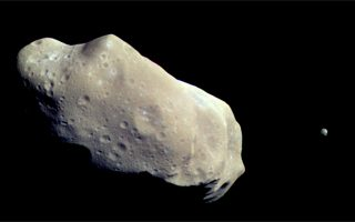** FILE **A color image of asteroid 243 Ida, taken by NASA's Galileo spacecraft, is shown in this Aug. 28, 1993, file photo. Ida's moon Dactyl is visible to the right of the asteroid. Galileo is on track to conclude its 14-year, $1.5 billion exploration of Jupiter and its moons on Sunday, Sept. 21, 2003 with a streaking suicide plunge into the planet's turbulent atmosphere. (AP Photo/Jet Propulsion Laboratory, File)