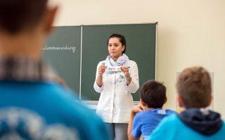 Η δασκάλα επιδεικνύει καρτελάκι που αναγράφει το όνομα «Mohamed» σε μια προπαρασκευαστική τάξη προσφύγων σε σχολείο της Γερμανίας.