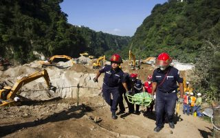 epa04963291 Rescue workers recover the corpse number 88 after a landslide that have left at least 88 dead and 350 missing people, in Cambray II village, Santa Catarina Pinula, Guatemala, 04 October 2015. Landslide took place on 01 October 2015 when heavy rains saturated the soil.  EPA/ESTEBAN BIBA