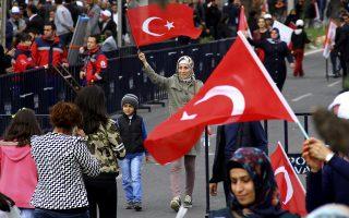 Ψηφοφόρος του κυβερνώντος κόμματος κυματίζοντας την τουρκική σημαία συμμετέχει μαζί με το παιδί της σε διαδήλωση, χθες, στο Ντιγιαρμπακίρ της Τουρκίας.