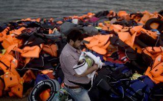 Ενας άντρας με το μωρό του αγκαλιά, σε ακτή της Λέσβου. Σήμερα στο ακριτικό νησί υπολογίζεται ότι βρίσκονται περίπου 11.000-12.000 πρόσφυγες και μετανάστες.