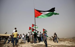 Demonstrators place Palestinian flags as they celebrate after the U.N. General Assembly overwhelmingly approved a Palestinian-drafted resolution to fly Palestine's flag at United Nations headquarters, during a protest against Jewish settlements in the occupied West Bank village of Nabi Saleh near Ramallah, September 11, 2015. There were 119 votes in favor out of 193 U.N. members.The United States and Israel were among eight countries that voted against the Palestinian-drafted resolution, which says the flags of non-member observer states like Palestine