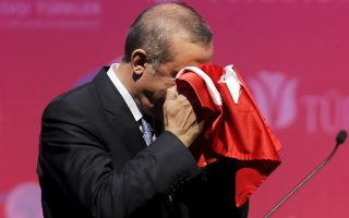 Turkey's President Tayyip Erdogan kisses a handmade Turkish flag, given to him as a gift from Ugandan university student Cemil (not pictured), during a graduation ceremony in Ankara, Turkey, June 11, 2015. President Erdogan on Thursday urged the country's political parties to work quickly to form a new government, saying egos should be left aside and that history would judge anyone who left Turkey in limbo. In his first public appearance since Sunday's parliamentary election, Erdogan said no political development should be allowed to threaten Turkey's gains. He said he would do his part in finding a solution with the powers given to him by the constitution. REUTERS/Umit Bektas TPX IMAGES OF THE DAY
