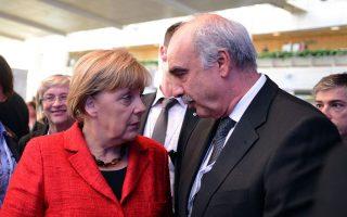 Ευ. Μεϊμαράκης και Αγκελα Μέρκελ συνομιλούν στο περιθώριο του συνεδρίου του ΕΛΚ, στη Μαδρίτη.