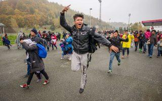Πρόσφυγες και μετανάστες, μερικοί με παιδιά στην αγκαλιά, διασχίζουν τα σύνορα Σλοβενίας - Αυστρίας.