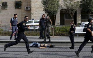 Iσραηλινοί αστυνομικοί στέκονται δίπλα από τη σορό Παλαιστινίου που προσπάθησε να μαχαιρώσει δύο ομοεθνείς τους στην Ανατολική Ιερουσαλήμ.
