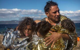 Ενας άνδρας στη Λέσβο κρατάει τρία παιδιά που βγήκαν ζωντανά από το ναυάγιο της περασμένης Τετάρτης, όταν ξύλινο σκάφος ανοιχτά του Μολύβου, με περισσότερους από 300 πρόσφυγες, ανετράπη. Δεν ήταν όλοι το ίδιο τυχεροί.