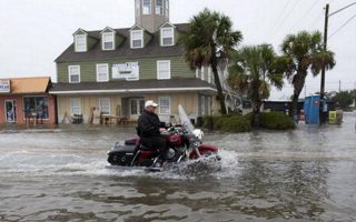 A motorcyclist navigates through flood waters in Garden City Beach, South Carolina, October 2, 2015. Category 4 Hurricane Joaquin is now moving northward and has started bringing swells to parts of the southeastern coast of the United States, the National Hurricane Center said on Friday. REUTERS/Randall Hill