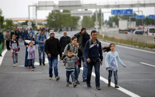 Migrants walk on a highway towards Vienna, near Nickelsdorf, Austria September 11, 2015. The train link between Austria and Hungary will remain closed through the weekend because of the continued strain on the system from the large inflow of migrants, the Austrian rail operator OeBB said in a statement on Friday. REUTERS/Leonhard Foeger