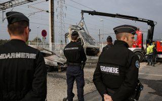 Καμένα αυτοκίνητα αποσύρει γερανός, παρουσία αστυνομικών.