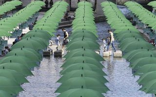 Visitors walk under umbrellas on display over Cheonggye stream during a campaign to raise donations to help underprivileged children in Seoul, South Korea, Tuesday, Sept. 29, 2015. (AP Photo/Ahn Young-joon)