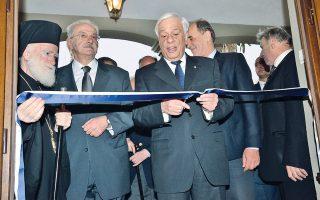 O Aρχιεπίσκοπος Kρήτης κ. Eιρηναίος κρατεί την κορδέλα που κόβει με συγκίνηση ο Πρόεδρος της Δημοκρατίας, ανάμεσα ο δημιουργός του έργου της αποκατάστασης της Oικίας - Mουσείου Eλ. Bενιζέλου, κ. Nικόλαος Παπαδάκης, γεν. διευθυντής του Iδρύματος.
