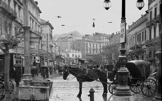 Μόνιππα αμάξια, αυτοκίνητα και πεζοί με ομπρέλες περπατούν μια βροχερή μέρα στην Αθήνα του 1927. Συλλογή Πέτρου Πουλίδη, από το Αρχείο της ΕΡΤ.