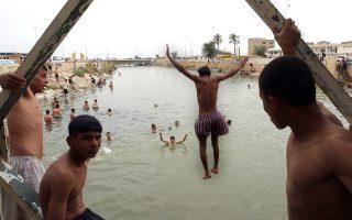 Ενας νεαρός Ιρακινός πηδάει στο μολυσμένο ποτάμι Σατ αλ Αράμπ από μία γέφυρα στο κέντρο της Μπάσρα.