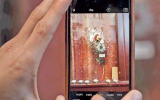 Ανδρας χρησιμοποιεί το τηλέφωνό του για να φωτογραφίσει το «Λε Καριγιόν», λίγες ώρες μετά τη σφαγή.