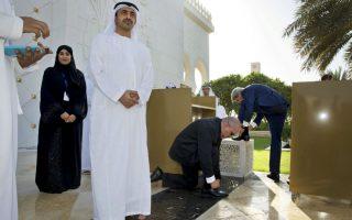 Γιατί οι Άραβες φορούν σανδάλια. Ο υπουργός Εξωτερικών των Εμιράτων Abdullah bin Zayed Al Nahyan περιμένει υπομονετικά τον John Kerry και τα μέλη της συνοδείας του να δέσουν σκυμμένοι τα κορδόνια των παπουτσιών τους, μετά την επίσκεψή τους στο μεγάλο τέμενος  Sheikh Zayed του  Abu Dhabi στην διάρκεια επίσημης επίσκεψης του υπουργού Εξωτερικών των ΗΠΑ στην χώρα. REUTERS/Jacquelyn Martin/Pool